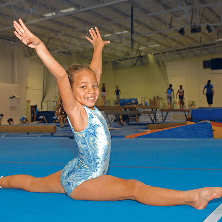 Young girl doing splits in gymnastics class