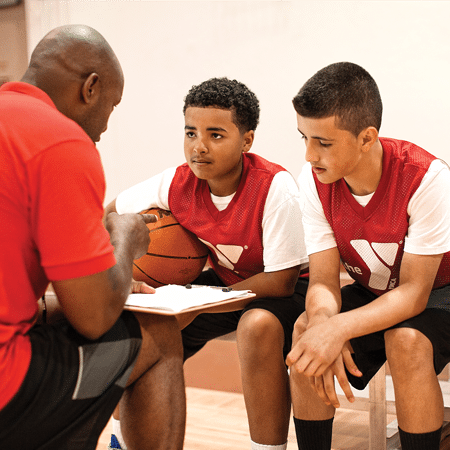 Teenagers in basketball huddle with coach