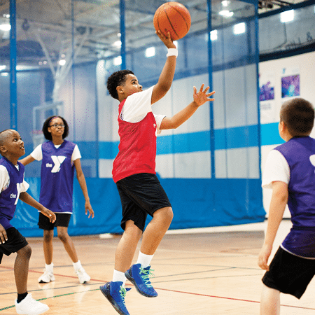 Boy shooting ball in competitive basketball league