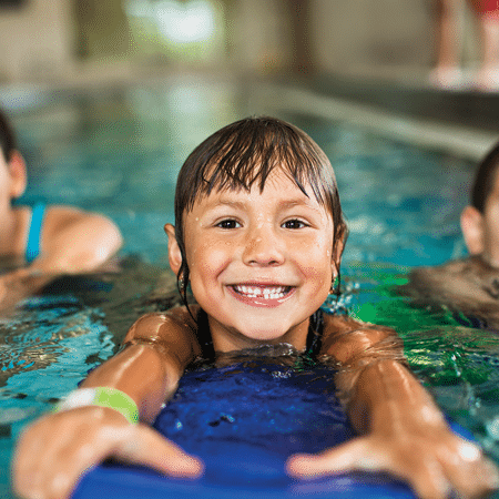 Young girl in swim lessons using kickboard