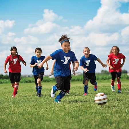 Youth soccer team chasing ball