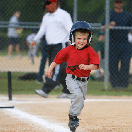 Young boy running bases after hitting ball