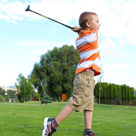 Young boy swinging at golf ball