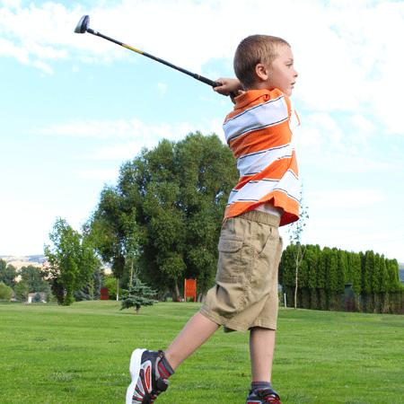 Young boy swinging at golf ball