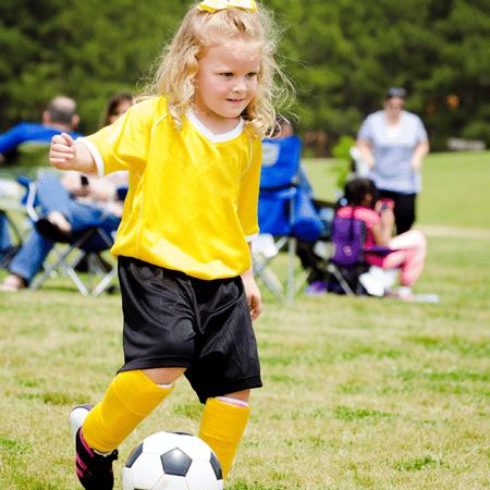 Young girl kicking soccer ball