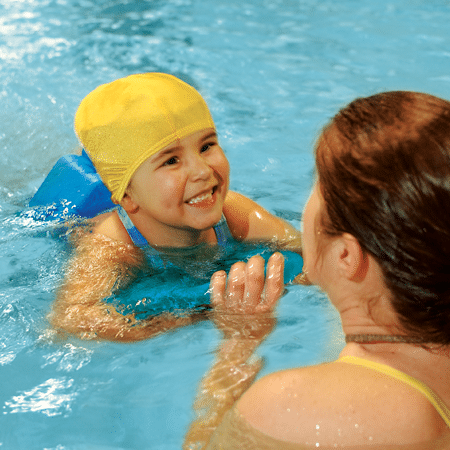 Young girl learning to swim with instructor