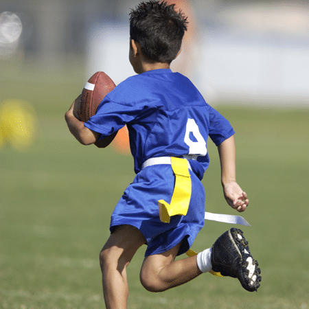 Young boy running with football