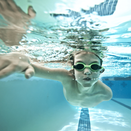 Boy swimming under water with goggles