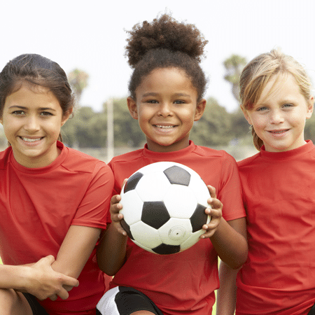 youth soccer players holding soccer ball