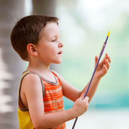 Young boy holding arrow in archery class