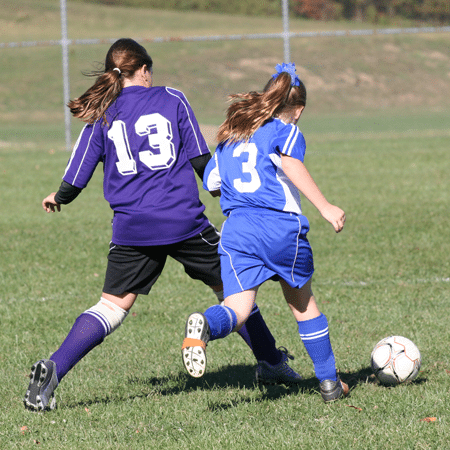 Girls chasing soccer ball in competitive soccer league game